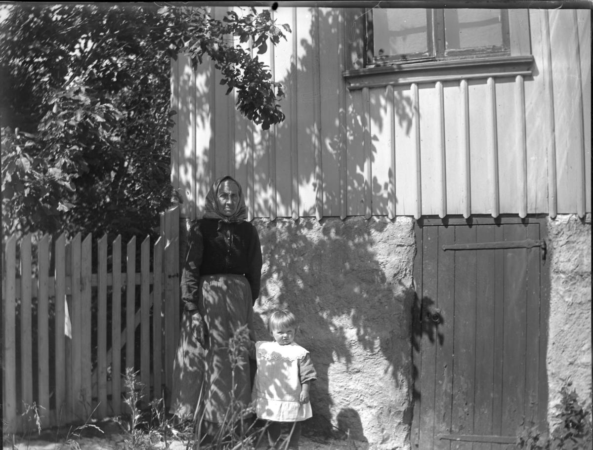 'Bildtext: ''Kyrkesund 1927.'' :: Vy med 1 gammal kvinna och ett litet barn, flicka, stående vid husgrunden till ett trähus, framför staket. Klädsel. ::  :: Ingår i serie med fotonr. 5228:1-11.'