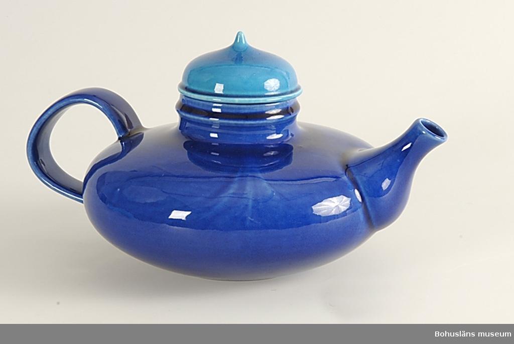 Form av tillplattat klot, mjuk pip, bandformad grepe.  Klart blåglaserad med mer blågrönt lock. Det berättas att modellen kom till när formgivaren i en fransk keramikfabrik drejade fram en Aladdinlampa. Idén tog hon sedan med sig till Rörstrand, där hon gjorde om lampan till en tekanna som presenterades år 1968. Tekannan blev en succé.  Ur Nationalencyklopedin: Persson, Inger, född 1936, keramisk formgivare, anställd vid Rörstrand 1959 - 1971 och från 1982 till mitten av 1990-talet. P:s serviser, bl.a. Spisa (1984) och Pro Arte (1994), utmärks av säker formkänsla. Några låga tekannor i starka färger med lock i avvikande färg från slutet av 1960-talet har liksom en serie stora skålar från 1988 rönt särskild uppmärksamhet.