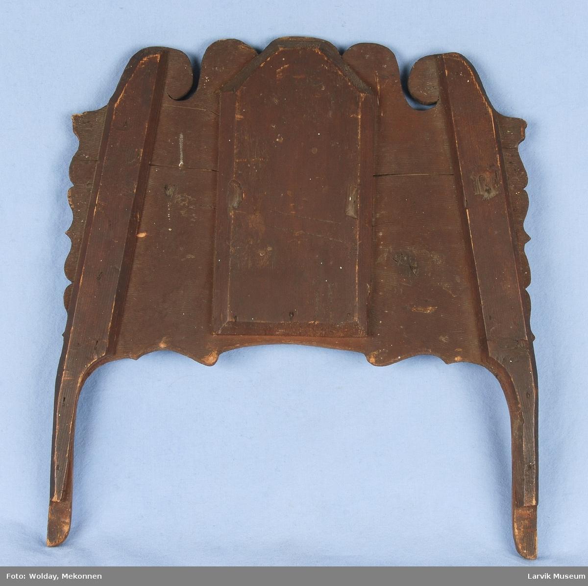 Form: Enkelt utskjærte kanter. snirklete med rett kant. Sirkelform på midten, med bladdekor. Pyntedelen på toppen av en speilramme.