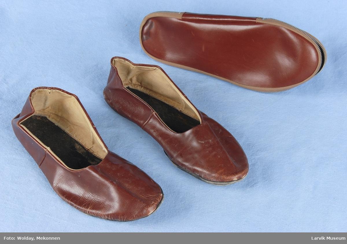 Form: etui i brunt skinn,bendelbånd og metallglidelås Tøflene i brunt skinn m svarte såler,lappet,foret delvis m lerret