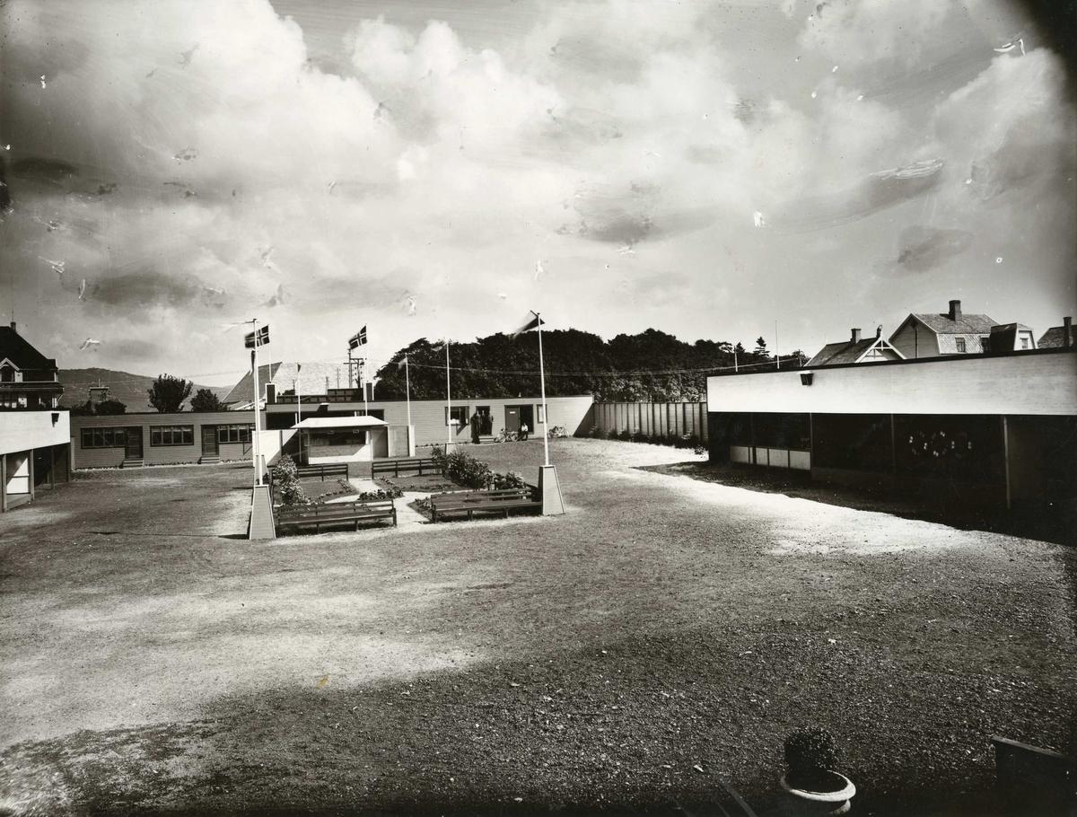 """""""Fornøyelsen"""" - fornøyelsesparken på Gard. Bildet er tatt fra scenen mot øst med murmester Sandes hus til v. i bakgrunnen og sannsynligvis Enok Nygårds løe mellom flaggene. Bildet er sannsynligvis av nyere dato i fornøyelsesparkens historie som sluttet ca. 1954. Den startet  i slutten av 1930-årene."""