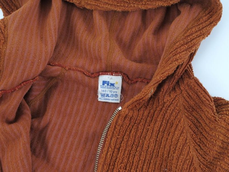 Hettejakke av cordfløyel. Med lommer og glidelås. Rustrød farge.