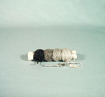 Nystpinne gjord av ett fårben. Upplindat ullgarn i fyra nyanser. Kostade 7:-, Gotlands Läns Hemslöjd.Framtagen på Ella Skoglunds tid som en souvenir.