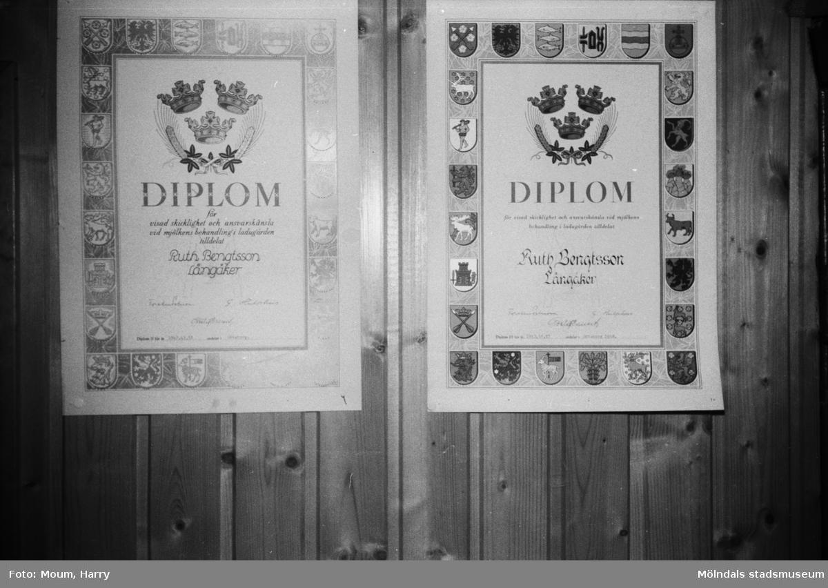 Två diplom utfärdade till Ruth Bengtsson hängandes på väggen i hembygdsgården i Långåker, Kållered, år 1983.  Fotografi taget av Harry Moum, HUM, Mölndals-Posten, vecka 41, år 1983.