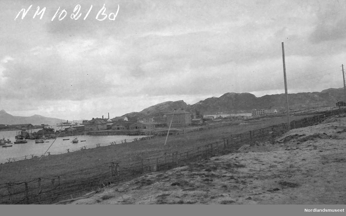 Mot byen, sett fra Breivika. Piggtrådsperringer. Båter på havna. Noen bygninger/ruiner helt i bakgrunnen.