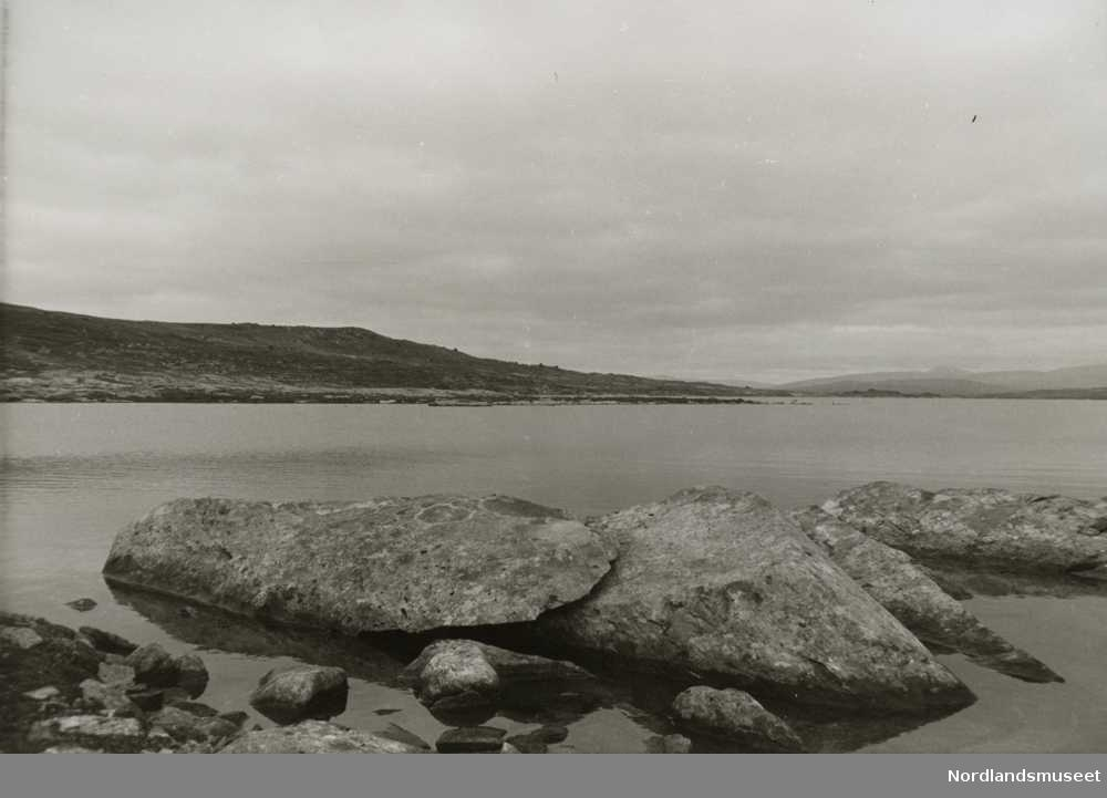 Fjord, fjell og fjæresteinene tatt fra Nasa, Silbjaure. Fjæra i forgrunnen. Fjellene i bakgrunnen. Overskyet.