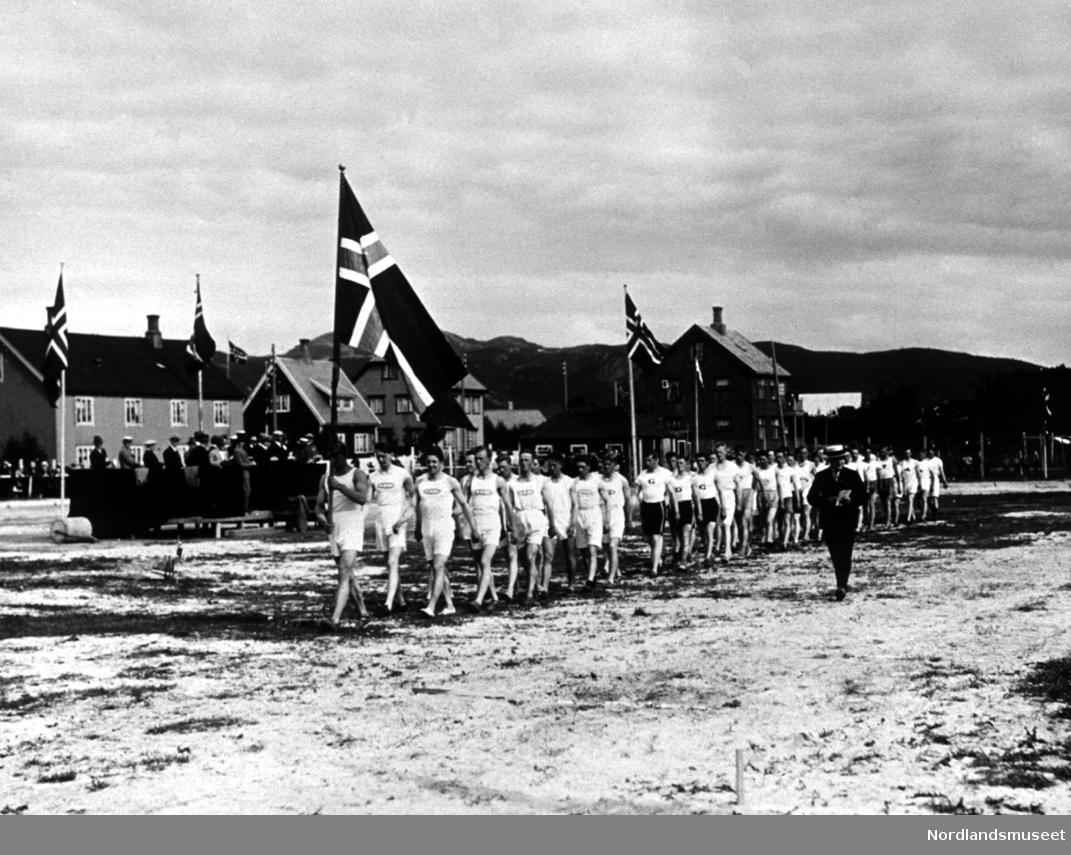 Turnere marsjerer. Idrettsplassen ved sykehuset. Bærer det norske flagg. Bygninger t.v. og flere tilskuere.