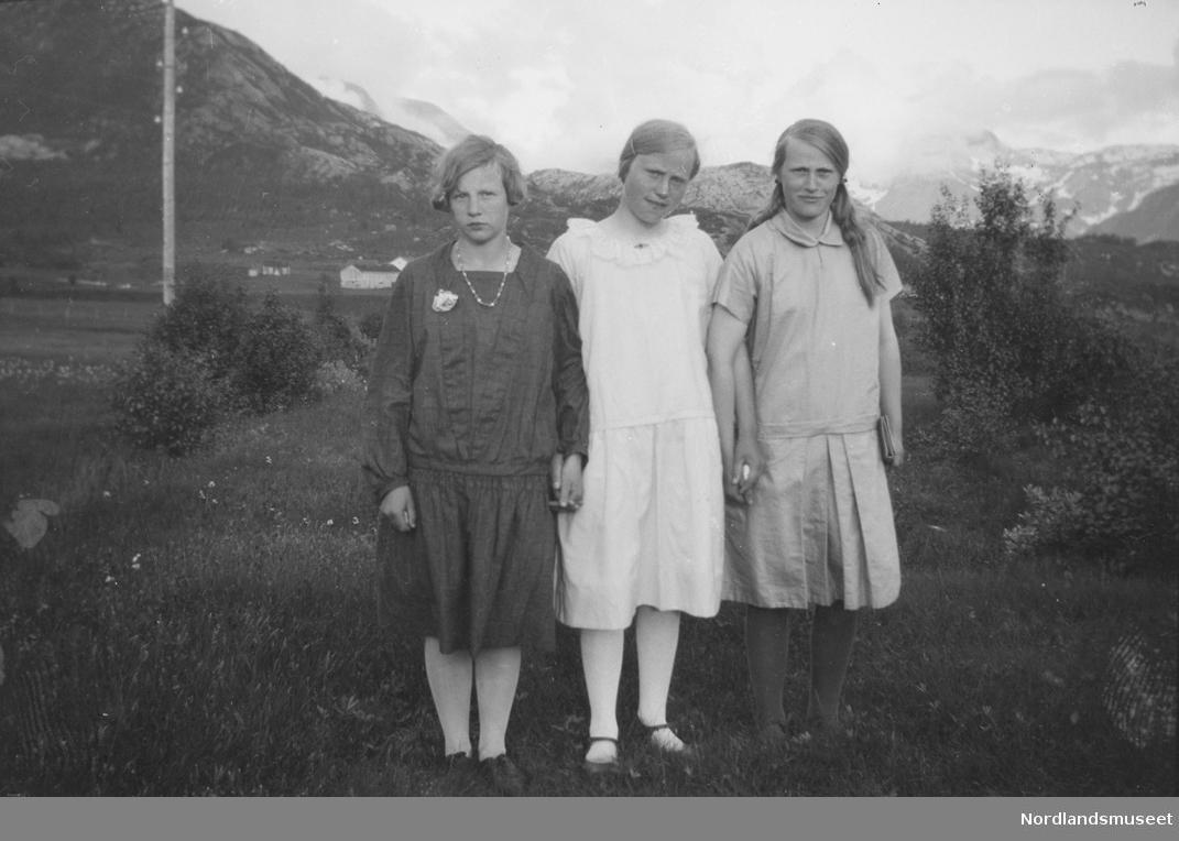 66576b3e Portrett av tre jenter. pent kledd. Hus, forsamlingshus og fjell i bakgrunn.
