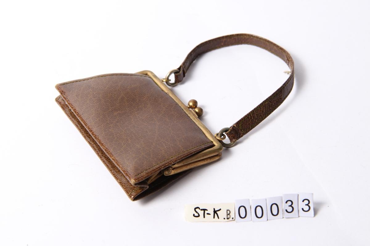 Pengepung i grønt skinn formet som liten veske med hank.