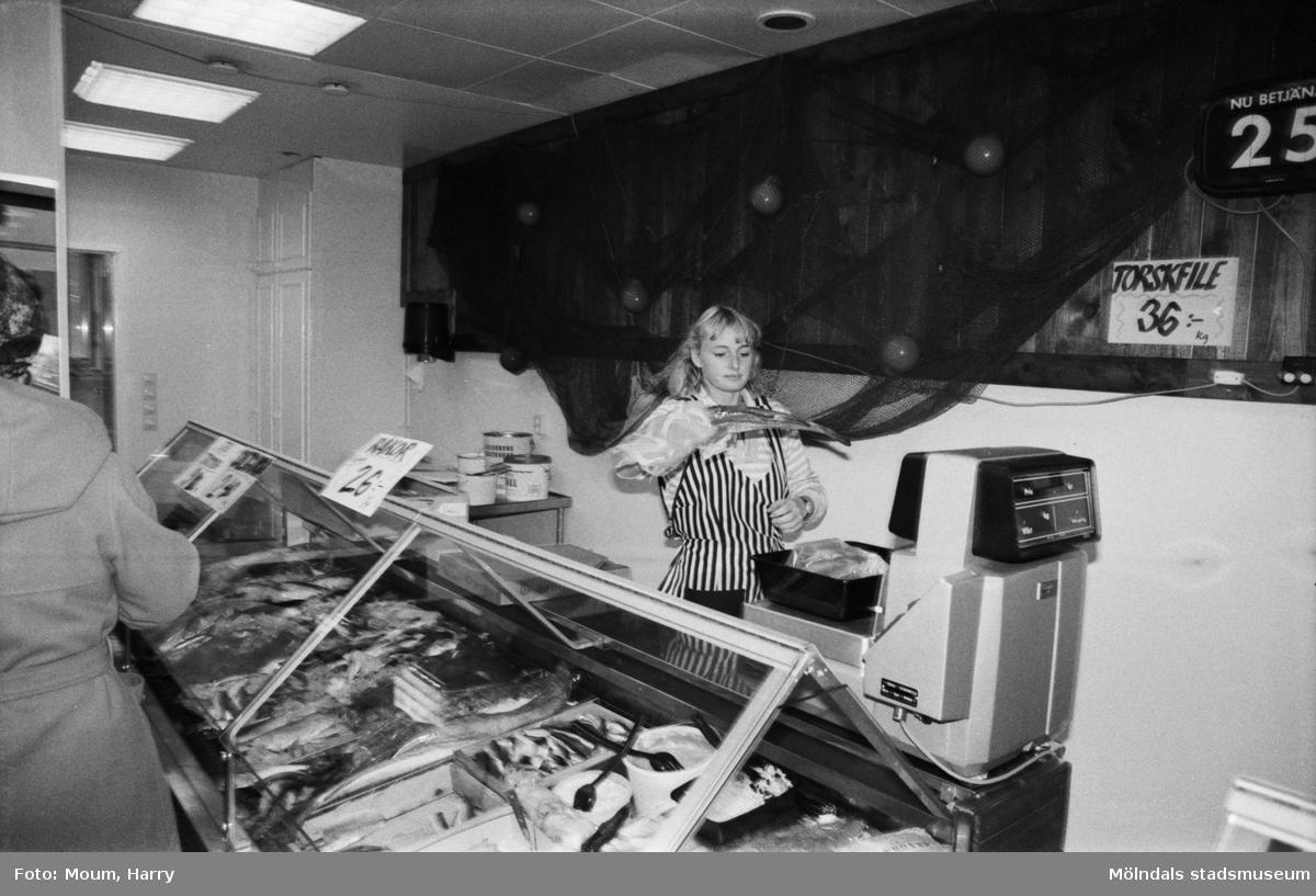 """Ny fiskaffär, Fiskhörnan, på Hagabäcksleden i Kållereds centrum, år 1983. """"Fina fisken. Christina Sjöbring på väg till vågen.""""  För mer information om bilden se under tilläggsinformation."""