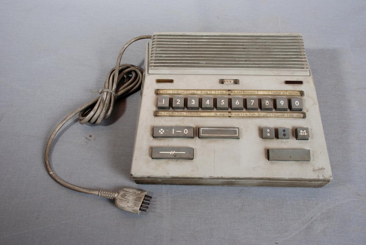 Telefonapparat med sentralfunksjon, høyttalende. Firkantet form med høyttaler på toppen, 10 taster nommerert fra 1-0. Ulike tastefunksjoner lenger ned på apparatet. Ledning for tilkopling til kontakt