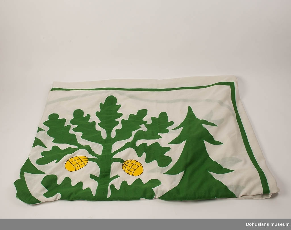 Flagga i vit polyesterväv med förstärkning genom dragsko med hisstamp av nylon med mässingshakar. Mitt på flaggan Uddevalla stadsvapen i grönt och gult, påsytt med sicksacksöm. Den vita väven är grånad.