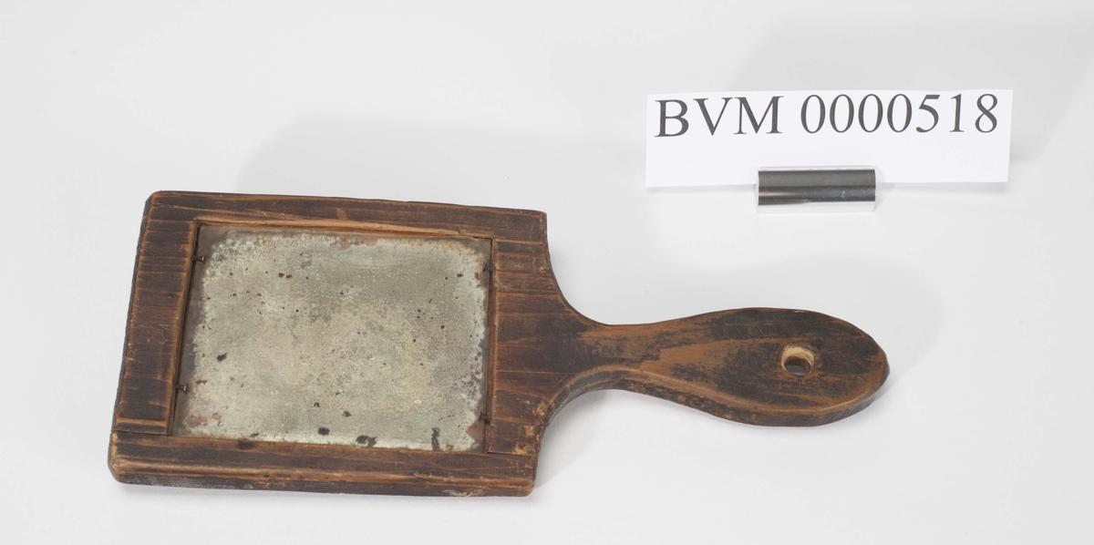 Hjemmelagd håndspeil med treramme med hull for oppheng i håndtaket.
