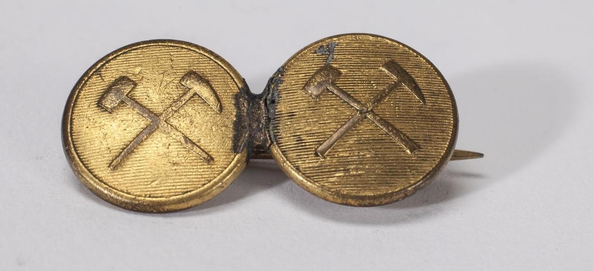 Brosje i messing med bergmannssymbol. Brosjen har trolig knekt i to og er reparert med lodding.