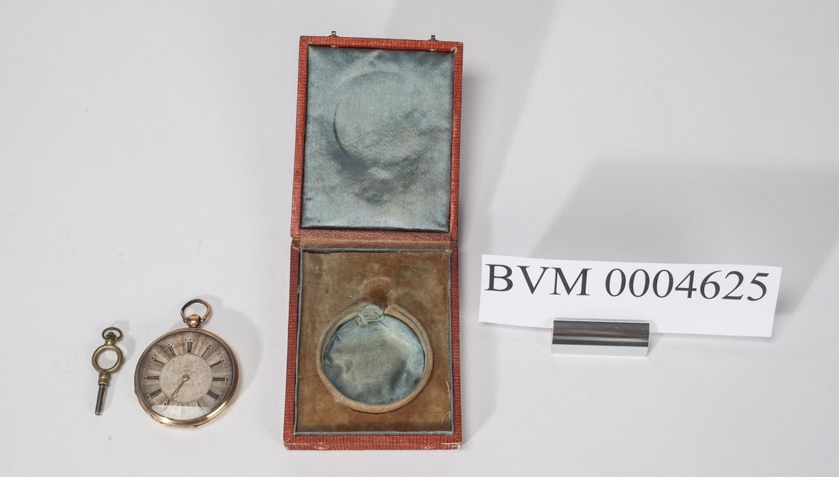 """Gullur med nøkkel til opptrekking liggende i en rød eske med gullfarget dekor. En lapp med bokstaven """"W"""" er limt på esken. Bak står """"9194 M. Weltz""""."""