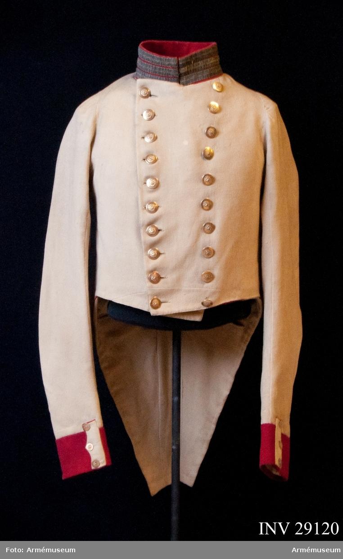 Grupp C I. Frack, vit, för officer vid K. Västgöta regemente med regementets vapen i knapparna; 1822-35. Beskrivning: Vit med röda uppslag och röd krage med silfver för officerare vid Västgöta regemente och vapnet i knapparna.