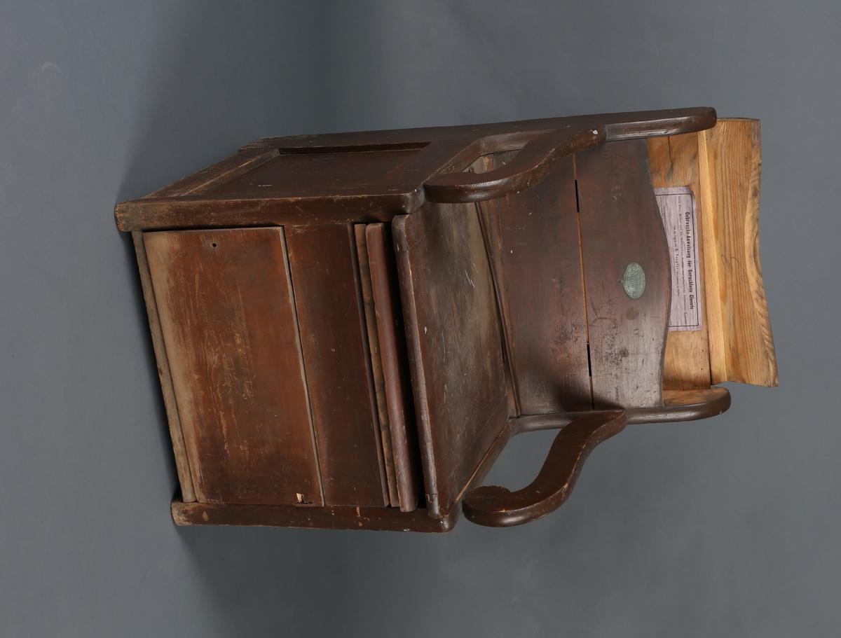 Stor dostol med 2 hengslede lokk . Det underste lokket med hull til bøtte, det øverste heldekkende sitteflate. Mellom disse, over hullet,  et lite løst lokk med knott. Hel ryggflate som er buet øverst, og utskårne armlener. Liten dør/luke med hengsler nederst. Buet list på ryggflaten.