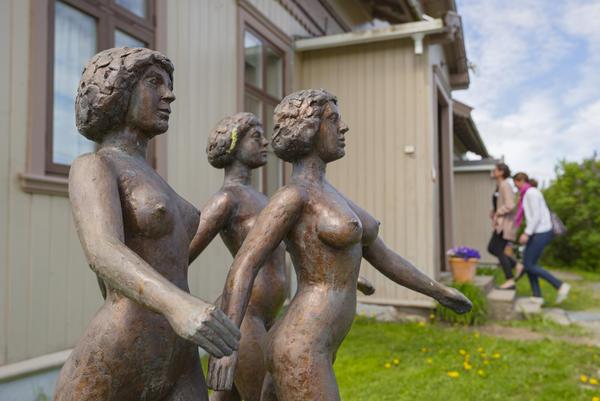 """To besøkende på veg inn til Kvinnemuseet. Skulpturen """"Nyfeministene kommer"""" i forgrunnen."""