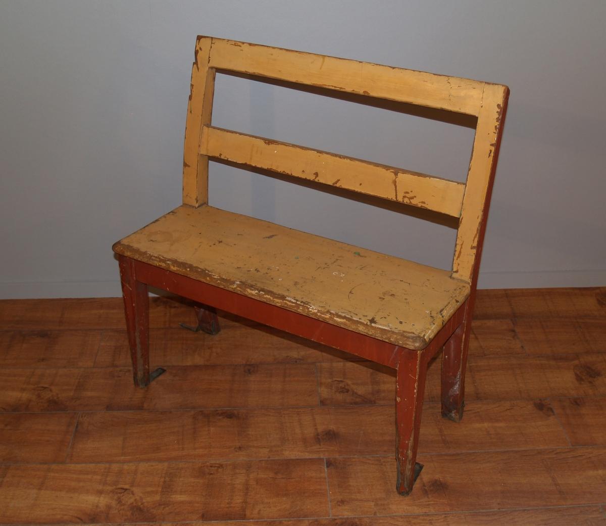 Benk med smale avlange seter med plass til 2. Fire ben og ryggstø. Deler av beslag på bena (til å feste i gulvet)