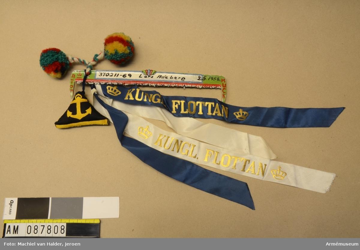 Muckarkam i plast som målats med färg och prytts med diverse vidhängande dekorationer i tyg och garn.