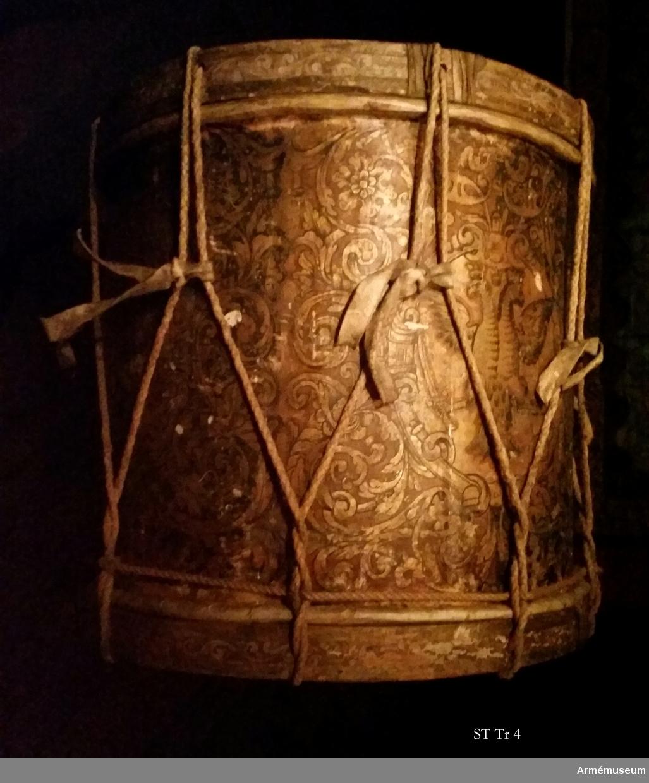 Cylindertrumma av trä, ursprungligen med två membraner. På guldgrund (gipslager undertill) utsmyckad med fyra medaljonger  med ryska dubbelörnen tillsammans med gyllene arkantusslingor på grön och brun botten.