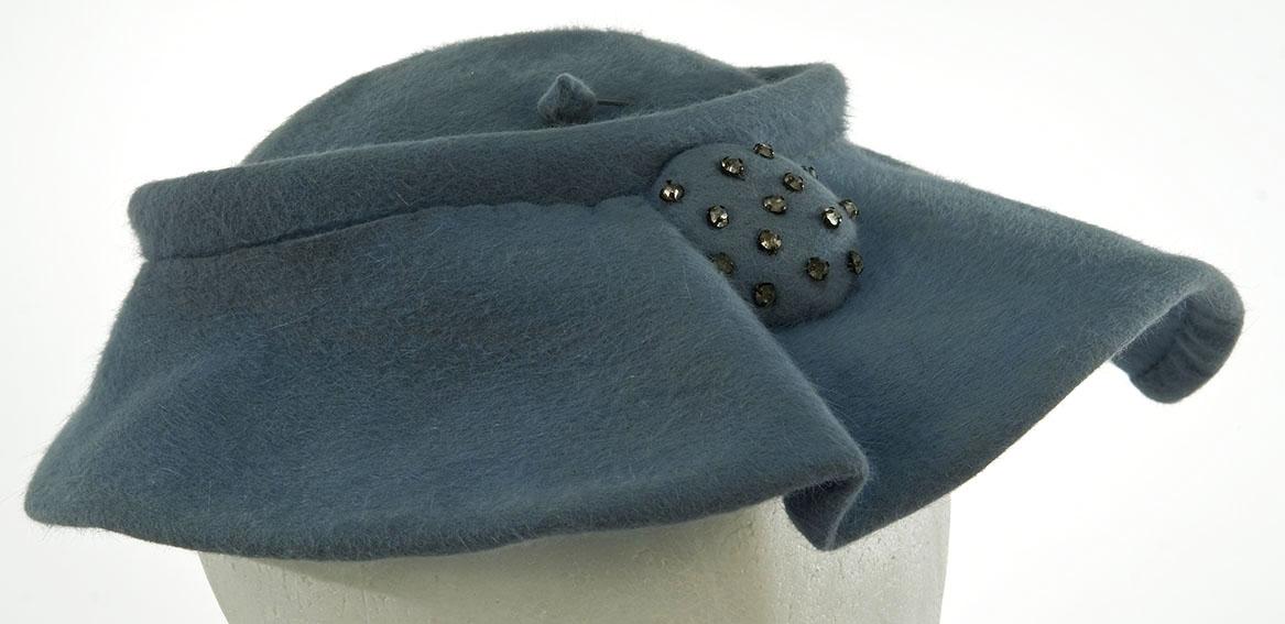 Baskerluefasong med en bise rundt toppen av pullen. Hattenål. Knappepynt med noen blanke stener