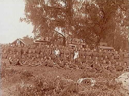 Inkallade soldater och två lottor vid I3 Regemente.I bakgrunden två bepansrade kulsprutevagnar och en kanon.