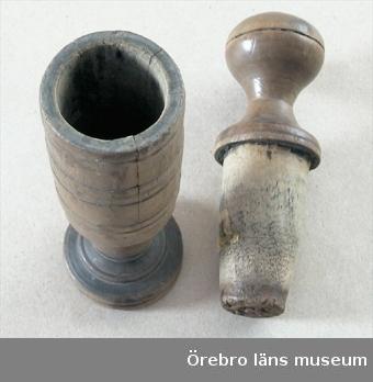 Kryddkvarn.  Består av två delar, dels mortel med rund fot, dels stöt. Morteln har formen av ett glas med mellanled mellan foten och själva formen. Formen har banddekor på utsidan. Stöten består av en rund knopp att hålla i och en nedåt avsmalnande trästöt. Stötens höjd 15,5 cm, diameter 5 cm. Gåva av Bror Pettersson, SvennevadNeg.nr.678/68