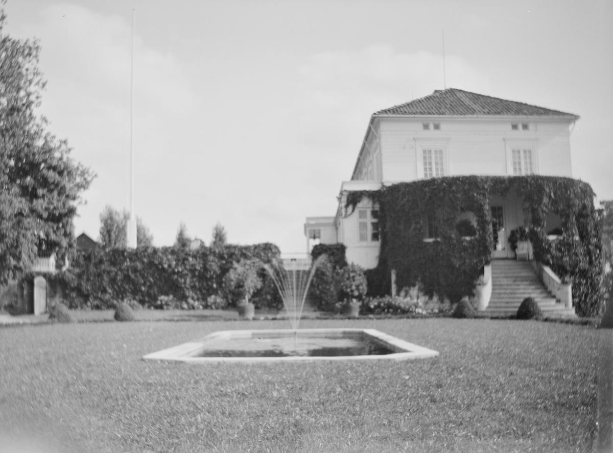 Hagen på Linderud Gård ved sommerstid. I front sees en avlang åttekantet dam med murkanter. I midten er det en fontene. I bakgrunnen sees friserte busker og hekker samt hovedhuset med en veranda som er dekket av klatreplanter, trapp opp til gårdsplassen med flaggstang.
