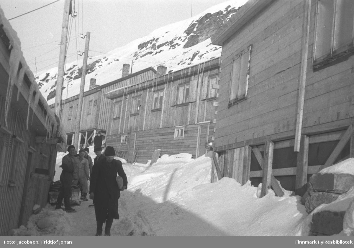 Salsgata i Hammerfest. Brakka bakerst i bildet tilhørte søstrene Andersen, og ble brukt som pensjonat, (brakka ble knust av et snøskred første påskedag 9.april i 1950). Brakkene står ganske tett og istapper henger fra takene. Flere av brakkene er bygd på påler. En smal gangvei, med mye snø på, går mellom brakkene. Flere el-stolper står på området og den bratte fjellsiden til Salen ses i bakgrunnen. Flere menn står på gangstien. De er kledt i vinterklær og luer på hodet.