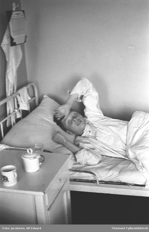 En gutt ligger i senga på St. Vincents Hospital. Senga har hvitlakkert ramme og hvite/lyse sengeklær. Gutten ligger på rygg og har en hvit pysjamasoverdel på seg. Han har armene oppover og den venstre håndbaken hviler han på panna si. Dyna er sammenbrettet og går opp til midja. Et hvitt/lyst nattbord står ved siden av senga. Oppå det står en kopp, et glass og et krus med lokk. Nattbordet har en skuff øverst og en skapdør under den. På sengegavlen henger et hvitt tøystykke. Bak sengegavelen står et stativ der det henger et oppslag, muligens informasjon til pasienter. Der henger også et stort tøystykke som kan være en håndduk. Veggene er ganske lyse og ensfarget.