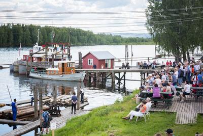 Foto av person på flåter i elva som demonstrerer bunting av tømmer, og publikum som sitter ved bord på land.
