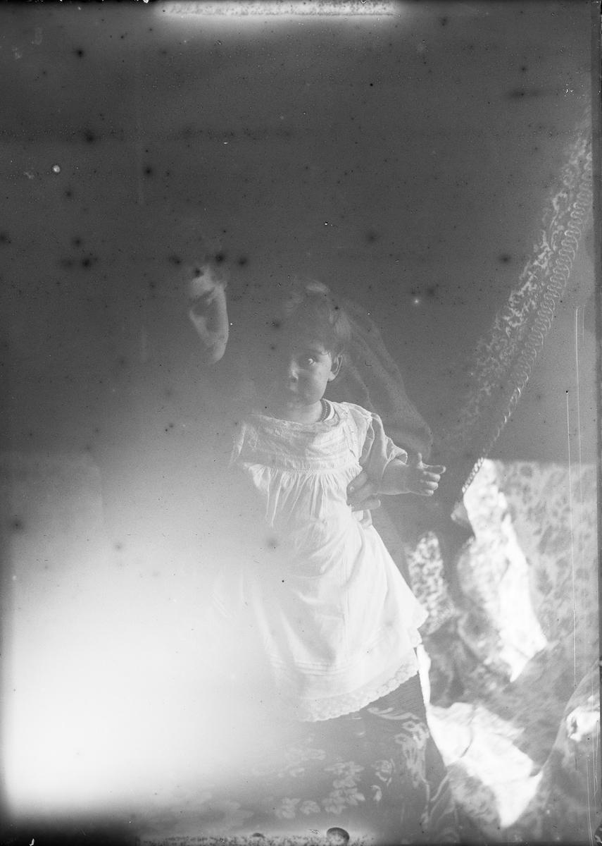 En kvinne holder et lite barn som står på en sofa. Lyset fra et vindu lyser opp motivet.