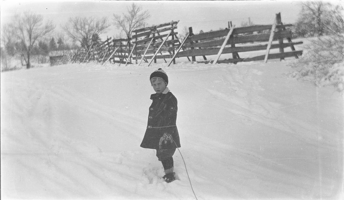 En gutt, trolig Iacob Ihlen Mathiesen, i vinterklær. I hånden holder han en snor; kanskje er det en kjelke festet til snoren?
