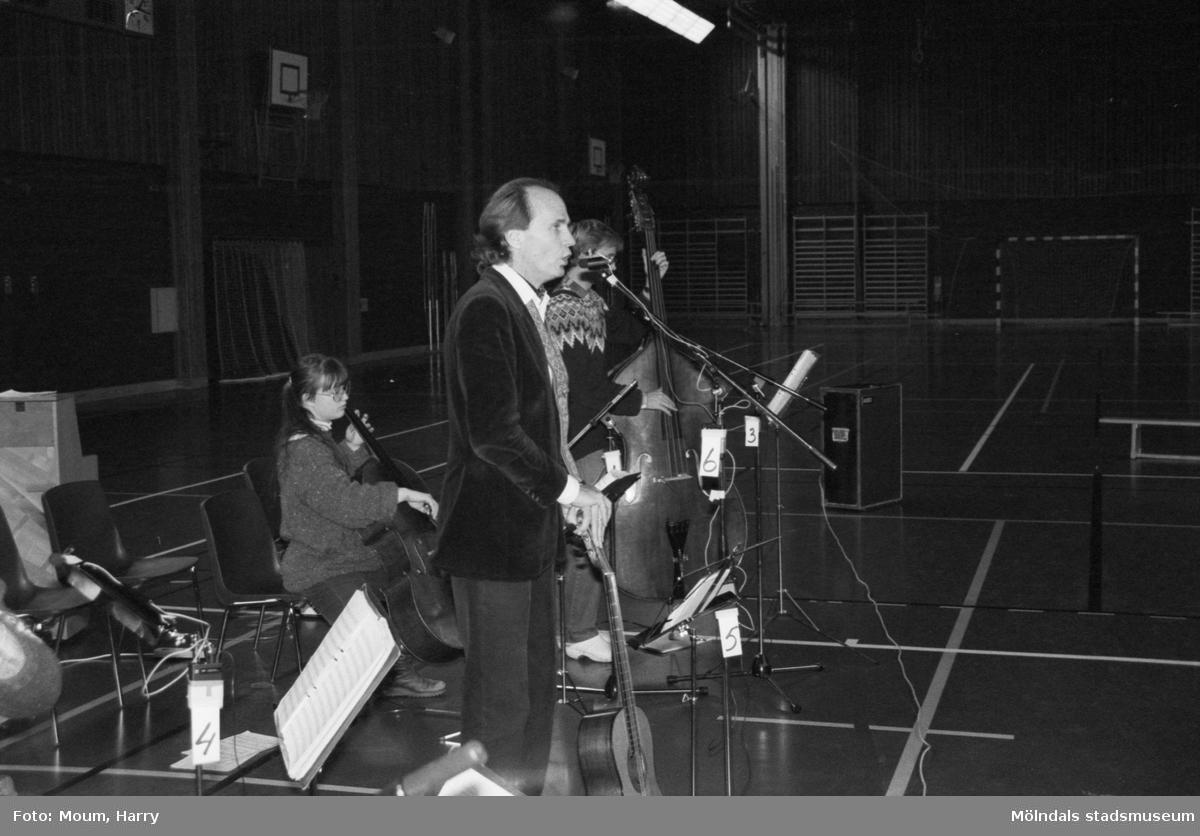 Trubaduren och viskompositören Alf Hambe håller tillsammans med gruppen Vindharpan konsert i Ekenskolans gymnastiksal i Kållered, år 1983.  För mer information om bilden se under tilläggsinformation.