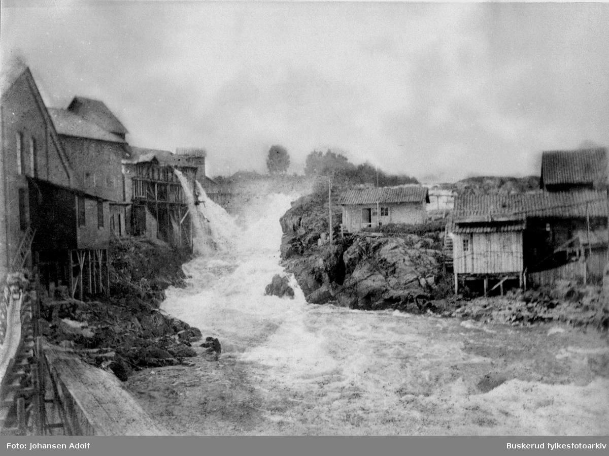 Hønefossen Fotografiet er fra Hønefossens midtre del - Høgbrofossen. Området ble nedbygd når den første kraftstasjonen i Hønefoss ble bygd. I dag liggerd et store sorte turbinrør i øvre del av dette området, og den nedre delen er gjenbygd. ca 1910