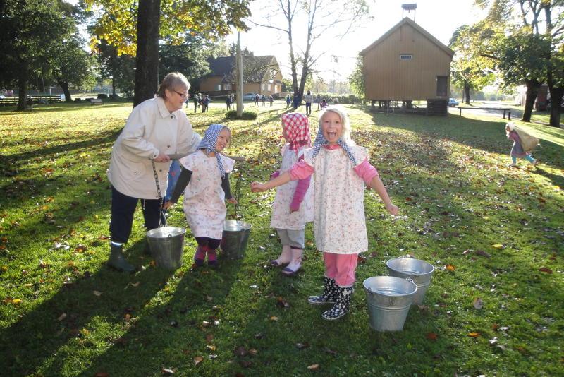 2. klassejenter i gammeldagse kjoleforklær og skaut som forsøker å bære vann med åk.