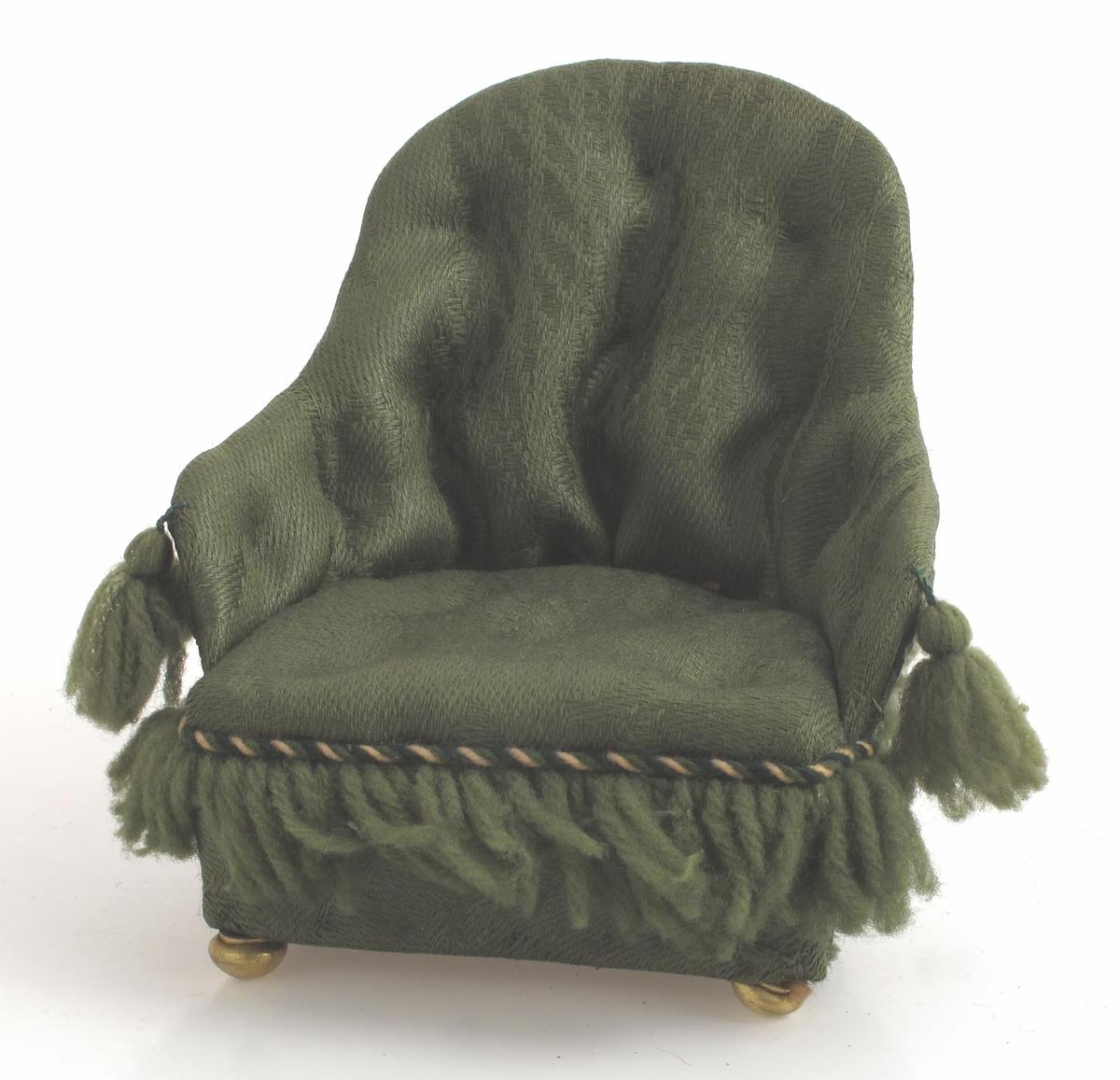 Lenestol trukket med grønn ulldamask.  Ullfrynser