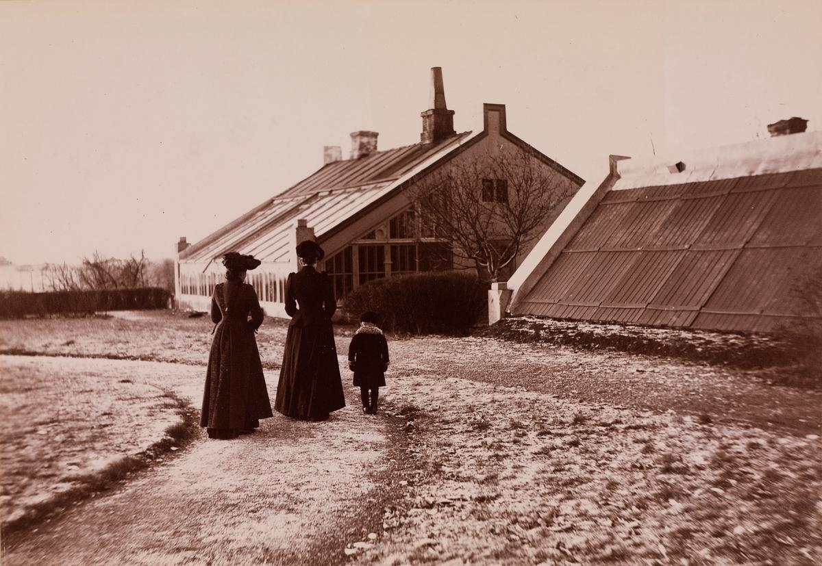 To kvinner og et barn foran veksthuset på Linderud Gård.
