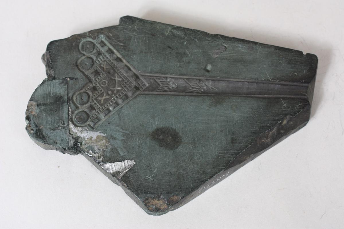 Form: Nesten trekanta Spenne til bunadslomme. Hjerteforma med krok. 5,3 cm. X 12,1 cm. på eine glattsida. 3 borrehol er tetta igjen. Knappeform på den andre glattsida har diam. 2,2 cm. Motiv av ein elg. Borra 2 hol, eit er tetta igjen.