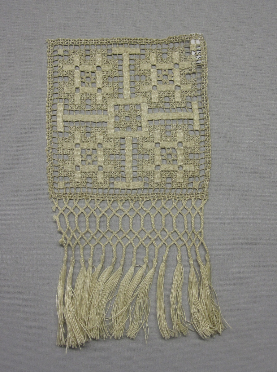 Prov på en filéknuten spets med trätt mönster, knutet och trätt. Den kvadratiska spetsen (150 x 150 mm) är kantad med treflätning och frans i en sida. Nät av rakställda rutor med fyra tätt trädda stjärnor i stoppstygn och glesare trätt/singlat mönster runt omkring. Halvblekt 3-trådigt s-tvinnat lingarn i nät. Trädning i halvblekt lingarn. Den iknutna treflätningen i halvblekt 1-trådigt z-spunnet lingarn.