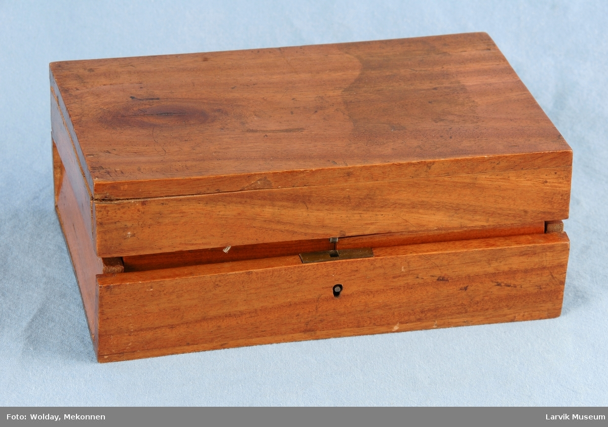 Form: messinglåsen er festet med messingskruer/selve åsbøylen er av jern.mess.-lokkhengsler festet med jernskruer. esken inneholder:2 stk kortstokker;1 rød og 1 blå mål:8,8x5,9cm,4 stk små esker med lokk.mål:8,7x5,1x3,9cm(L,B,H) hver av de små eskene inneholder:10 runde jetonger(D:2,9),10 avlange jetonger(1,8x5,6),5 nesten firkantede jetonger(5,1x3,9) rød og grønn:alle jetonger tilstede. gul:1 stk avlang mangler. lilla:1 stk rund skadet.