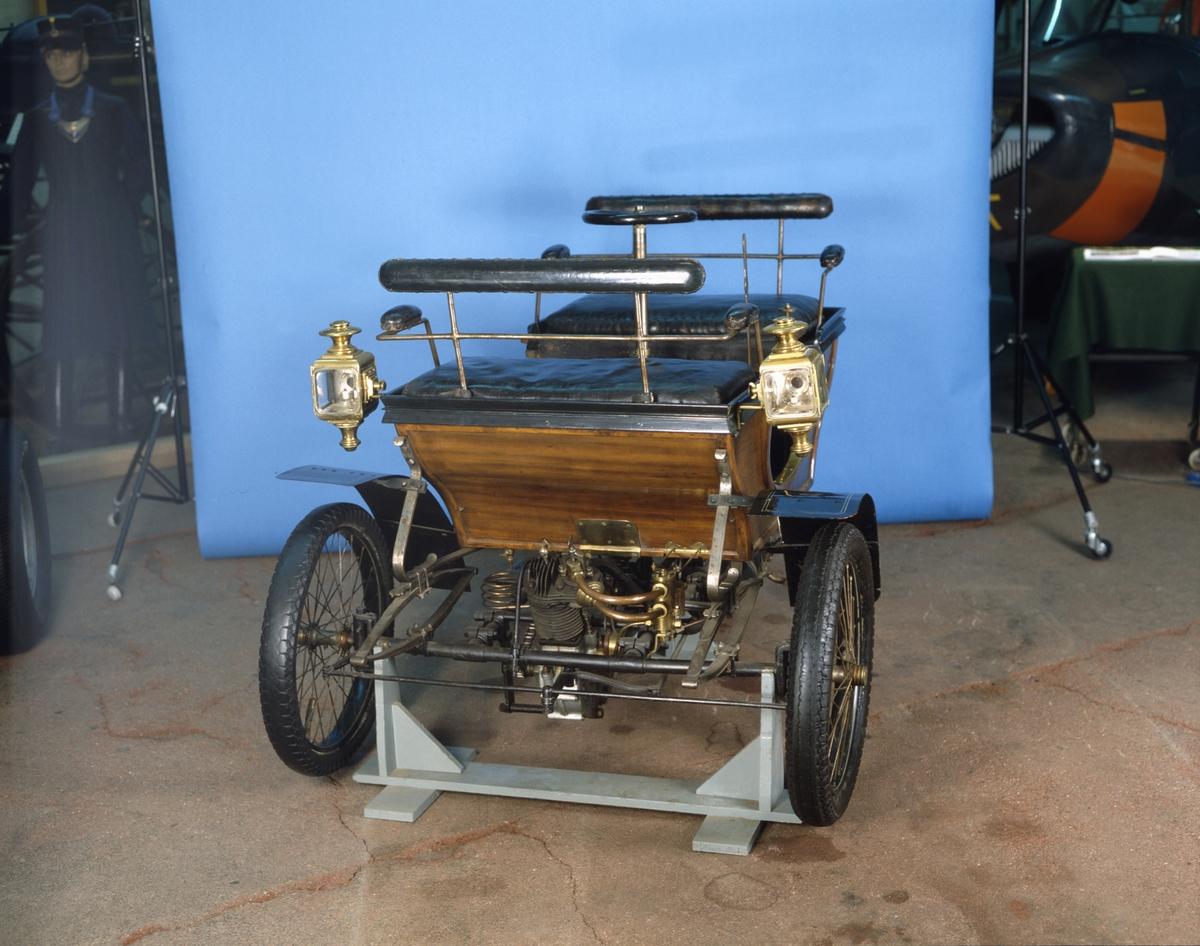 """Trehjulig bil med Kelecom, VAF & Co bensinmotor och en fransk förgasare. Kraftöverföring med kedja till bakhjulet. Bilen styrs med en ratt som sitter centralt placerad på en styrkolonn där övriga reglage också finns. Den har igen backinrättning men kan lätt av en person skjutas baklänges, bandbroms på drivhjulets nav. Fotbroms direkt på drifhjulets slitbana, som ej fanns vid bilens ankomst till TM. Karossen är av typ """"vis-a-vis"""" med plats för fyra och sannolikt tillverkad av mahogny.   Axelavstånd ca. 1500 mm, spårvidd: ca. 1150 mm, hjuldiam: ca. 650 mm. Motor märkt """"Moteur Relecom"""", """"VAF & Co"""", typ de Dion Bouton. Förgasare: Carburateur Longuemar 10176 brevté s.g.d.g.  Encylindrig luftkyld fyrtaktsmotor Cirka 2,5 hk Magnettändning och tändstift Två växlar, ingen backväxel Högsta fart 30 km/tim"""