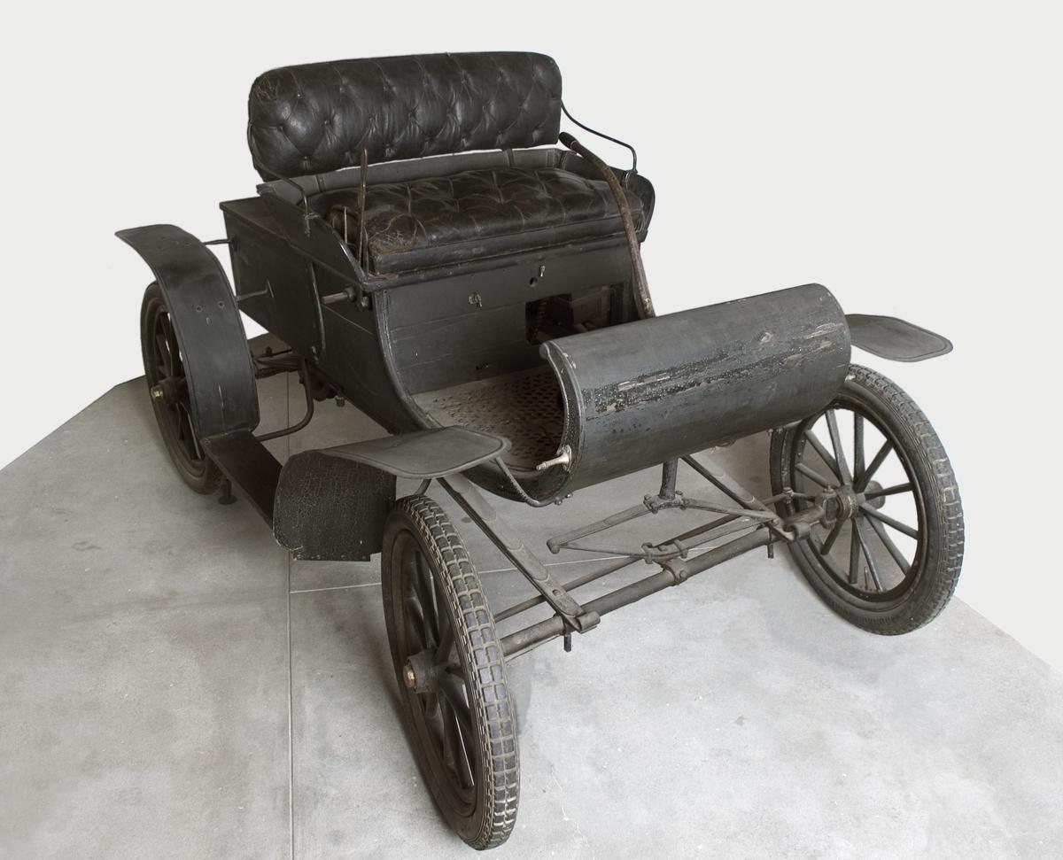 Oldsmobile 1904, för två personer, med bensin motor. Oldsmobile Curved Dash, modell R. Oldsmobile motor är placerad under sätet med cylindern under luckan baktill. Kraften överförs med kedja till bakaxeln, vevstart och styrning sker med spak. Halvelliptiska bladfjädrar i bilens längdsriktning. Kaross av trä med metallförstärkning. Batteritändning insatt senare. 3-30 km/tim. Normalt 1 L gasolja/mil. Motornr. 8226.  Luftkyld fyrtakts bensinmotor Cylindervolym 1 565 cc 4,5 hk vid 600 varv/minut Planetväxellåda med två växlar samt backväxel Högsta fart cirka 35 km/tim