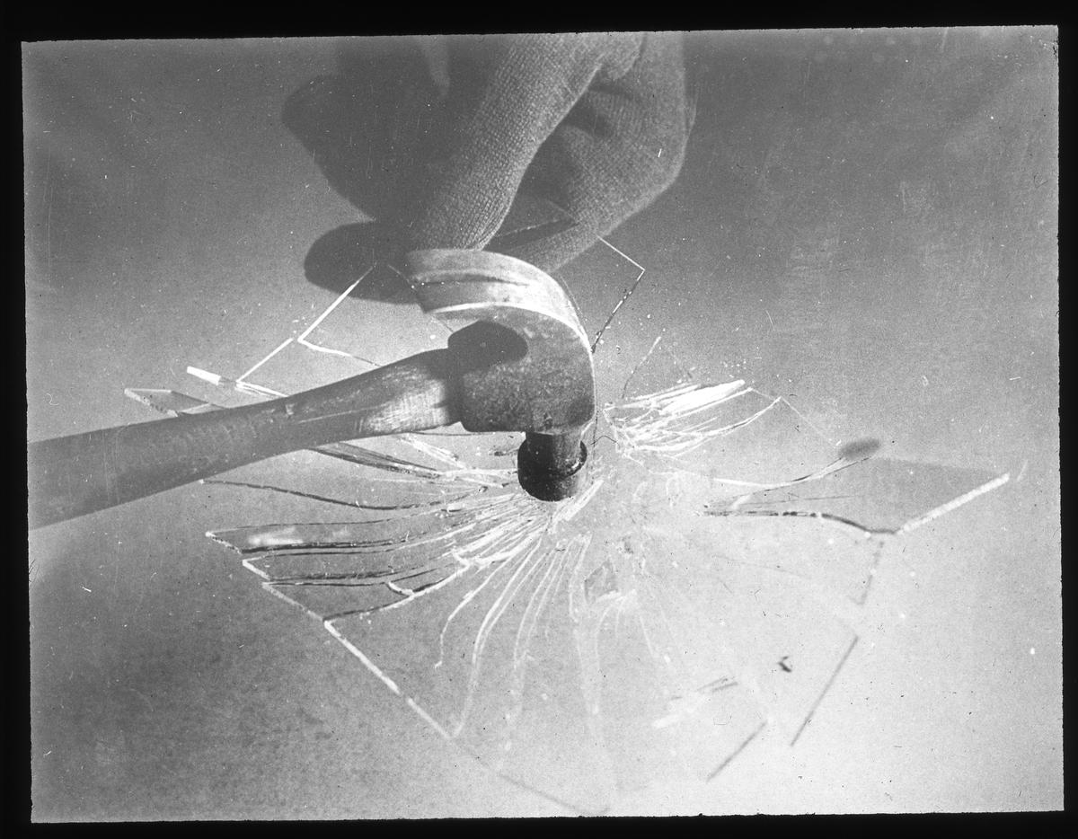 Skioptikonbild från Institutionen för fotografi vid Kungliga Tekniska Högskolan. Använd av professor Helmer Bäckström som föreläsningsmaterial. Bäckström var Sveriges första professor i fotografi vid Kungliga Tekniska Högskolan i Stockholm 1948-1958. Fotografi av hammare mot glas.