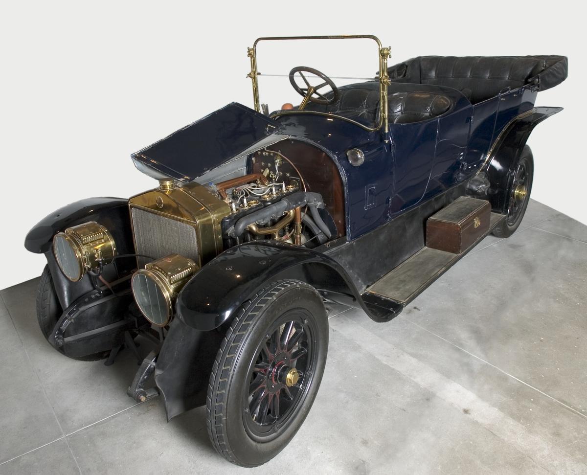 """Scania-Vabis, modell 1911. Furhjulig personbil med öppet karosseri. Karossen är tillverkad av mahogny på ekstomme. Fyra sittplatser samt två uppfällbara extrasäten bak. Rak fyrcyl. fyrtakts bensinmotor på 4,4 liter. Fyra växlar , kulissväxel med spaken utvändigt placerad . Magnettändning. Kylarsag lyktor m.m. är tillverkade av mässing. Gasbelysning samt två """"elektriska ögon på torpeden"""". Start med vev. Fartbroms på kardanaxel och handbroms på de två bakhjulen. Hjul med träekrar och stålfälgar.  30-36 hk enl katalog. Tillbehör: Två sidoskydd av segelduk."""