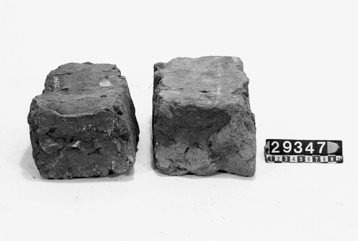 Tegelstenar den ena lagom bränd, den andra översintrad med grå färg. Handslagna. a) Längd: 250 mm, vikt: 4,6 kg. b) Längd: 250 mm, vikt: 4,2 kg.