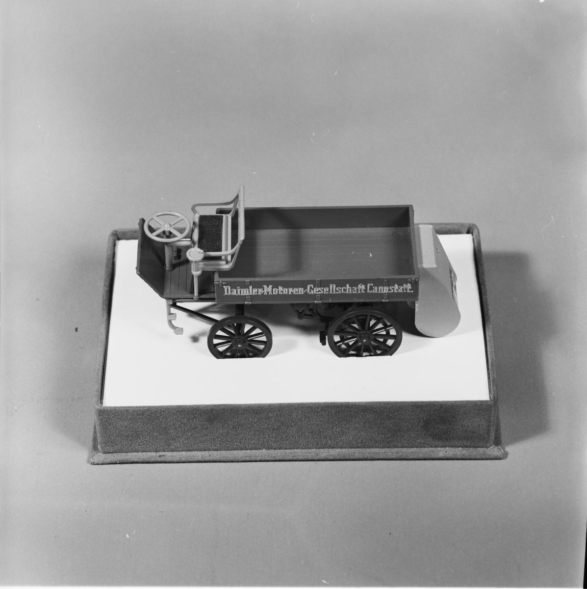 Modell av lastbil, gjuten i plast, beigefärgad med bruna hjul och svart chassi, flaklemmar med text. Hölje av plast. Lastbilens längd: 100 mm, bredd: 35 mm, höjd: 35 mm. Höljets längd: 120 mm, bredd: 85 mm, höjd: 68 mm. Märke: Daimler. Årgång: 1896.