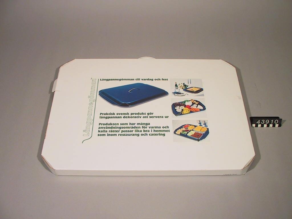 Bricka med lock. På brickan kan en hel ugnsplåt, långpanna, rymmas och serveringen direkt från långpannan kan därmed göras mer tilltalande. Locket används för att hålla maten varm, eller kall. Tillverkad av 3 mm formpressad furufanér, belagd med ett värmetåligt ytskikt av melamin.