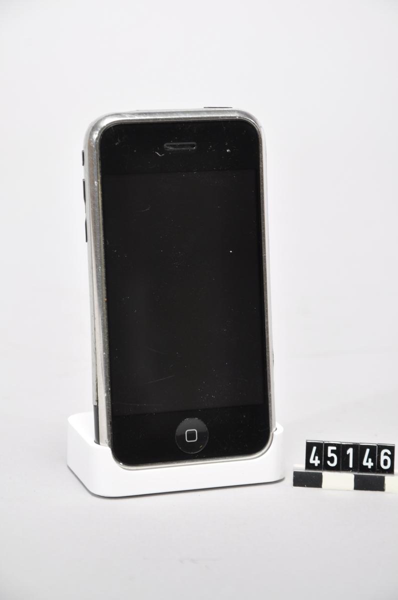 """Apple iPhone mobiltelefon för GSM med 8 GB inbyggt minne. I originalförpackning, med """"iPod"""" nätadapter för USB-anslutning, USB-kabel samt laddställ. Medföljande bruksanvisning.  Modell A1203, FCCID BCGA1203A, serienummer SK8318TTWH8, IMEI nr 011654001585174.  Apparaten är återställd till fabriksdata och fungerar ej med svenskt SIM-kort. Anvisningar och programvara för modifikation av telefonen återfinns på många websidor. Tillbehör: USB-laddare, USB-kabel, bordsställ"""